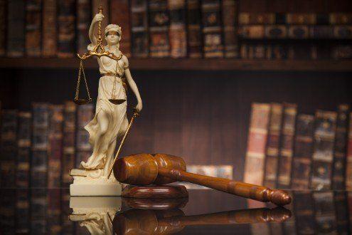 piccola statua della dea della giustizia e martello da giudice su una scrivania