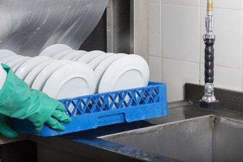 impiegato mette piatti nella lavastoviglie industriale