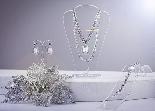 una parure di una collana, orecchini e un orologio in argento e cristalli