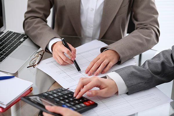 Accountants counting on calculator income for tax form completion