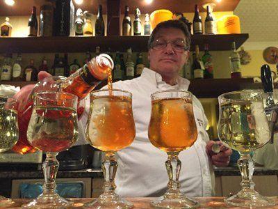 uomo al bancone di mentre riempie dei bicchieri con dell`alcool
