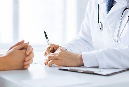 medico seduto alla scrivania con una penna in mano e di fronte una persona
