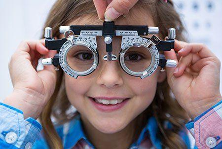 una bambina con degli occhiali specialistici per visita oculistica