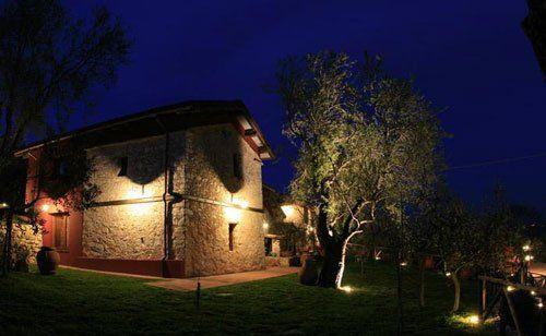 vista da lontano durante la notte di un edificio antico in pietra e un giardino con un ulivo e un lampione acceso