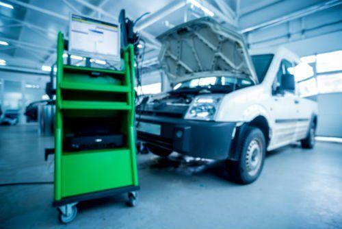 un carrello con un monitor e un furgone in officina