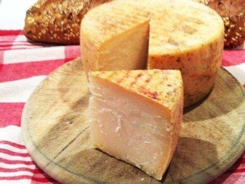 una forma di formaggio su un tagliere