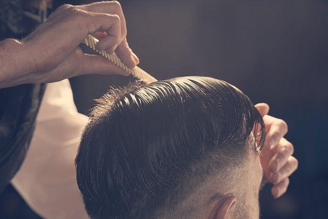 un parrucchiere che pettina un ragazzo