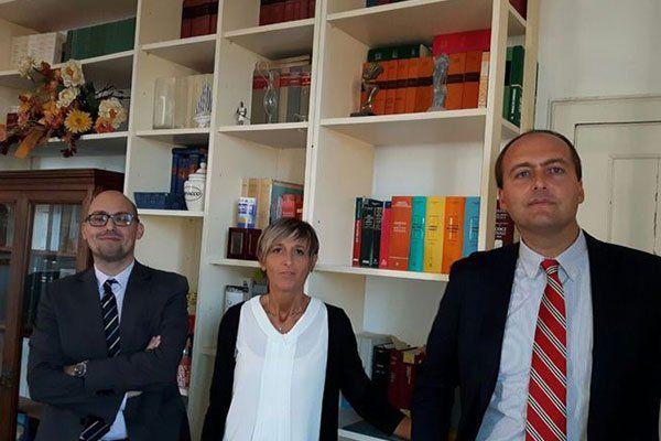 Tre avvocati, due uomini e una donna mentre posano per una fotografia