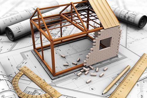 Un modellino di una casetta in costruzione sopra un progetto