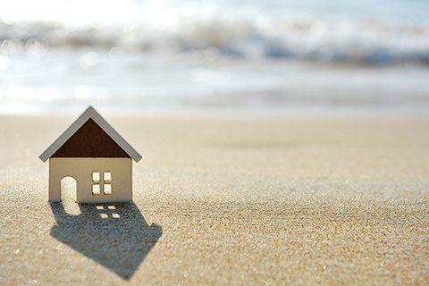 Il  modellino di una casa e sullo sfondo il mare