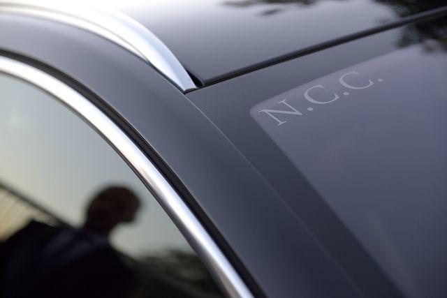macchina nera con riflesso dell'autista sullo specchio