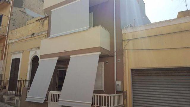 Dei balconi e sopra dei tendoni bianchi a righe verdi