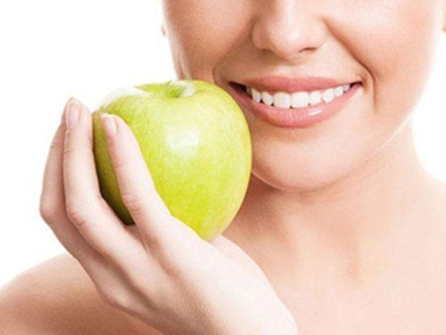 donna con denti bianchi e una mela