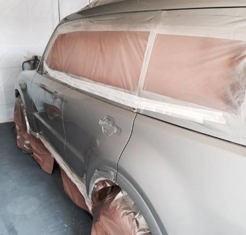 Auto sposi dipinto le cui finestre e ruote sono protette con materia plastica