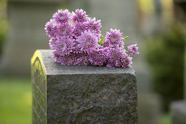 una lapide in pietra con sopra dei crisantemi