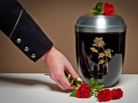 Mano che posa rose rosse vicino ad un'urna funeraria