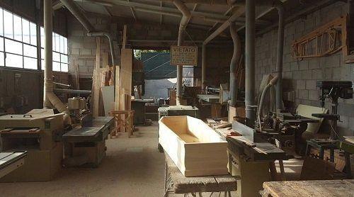 una bara in legno e l'interno di una falegnameria