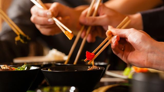 Young People Eating In A Restaurant With Chopsticks As Anchorage