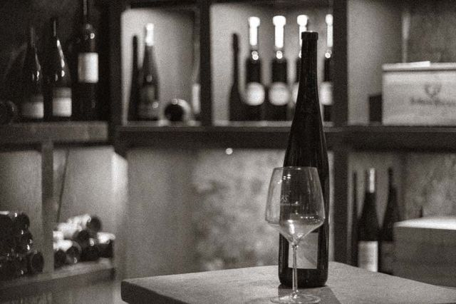 Close up of a wine bottle and wine glass in a wine cellar