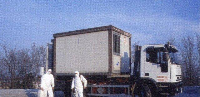 un camion bianco e due uomini con delle tute protettive