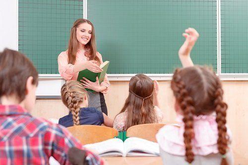 Bambina, che alza la mano in classe