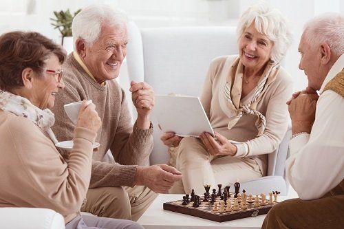 Due coppie che  parlano, sorridono  e giocano a scacchi