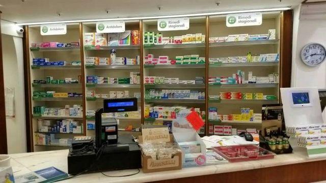 Quattro scaffali pieni di prodotti omeopatici da il banco della farmacia