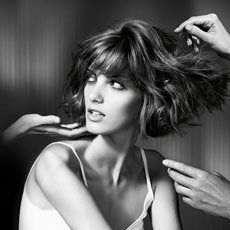 three hands checking female model's hair