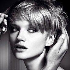 two hands assessing female model's short hair