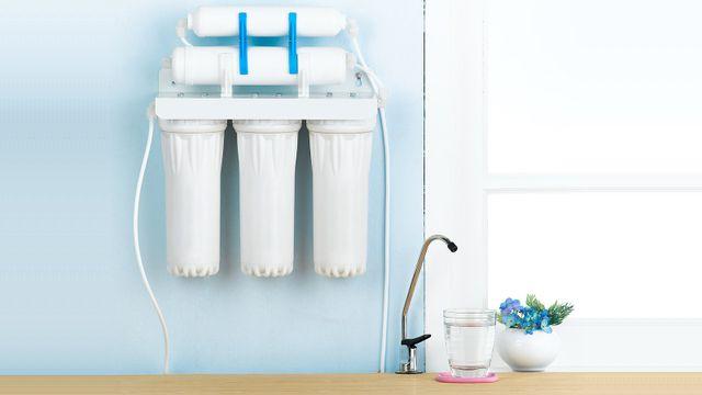 un depuratore d'acqua e sotto un rubinetto con accanto un bicchiere e un vaso di fiori blu