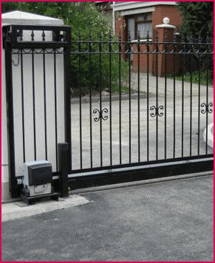 automatic bollards raised in front of a wrought iron gateway