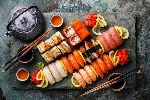 tagliere di sushi e sashimi con bacchette e the giapponesi
