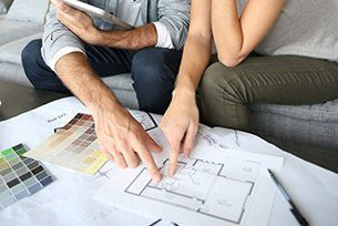 Couple looking over a custom building plan of their new home in Kamloops