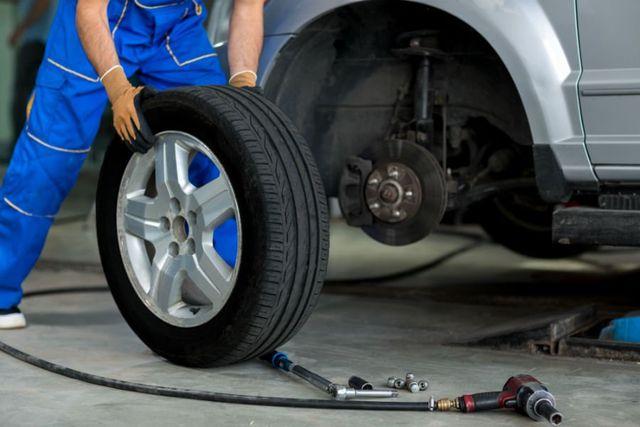 un gommista che sta cambiando una ruota di una macchina