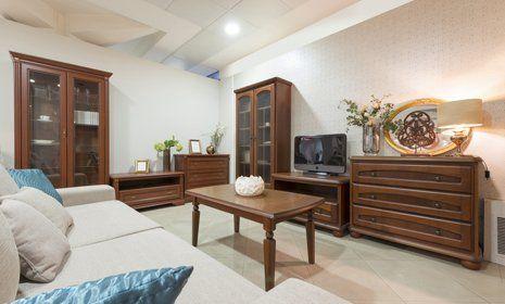 vista interna di una casa con cassetti in legno, vetrine in legno, tavolo in legno, televisione sul mensola in legno e divano con cuscini