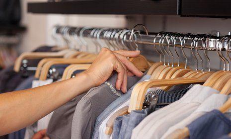 gente mentre controlla vestiti appesi su grucce in legno in un negozio