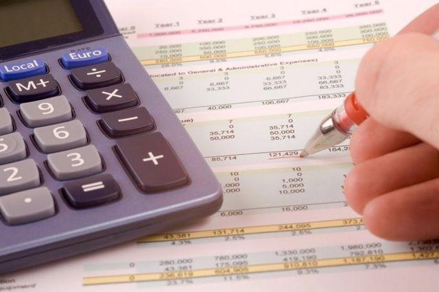 Man with calculator writing accountancy services in Archdale, NC