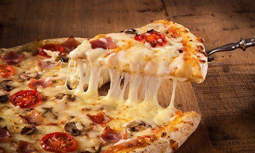 Formaggio fuso al tagliare la pizza di funghi e bacon con pomodoro fresco