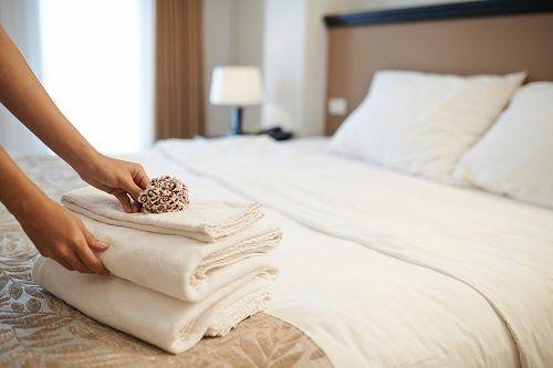 letto di un albergo con una pila di asciugamani