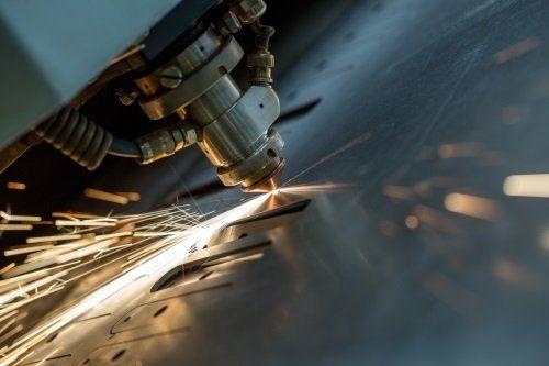 una punta di un macchinario che buca il ferro e delle scintille