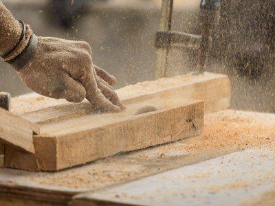 operaio taglia un'asse di legno con il macchinario apposito