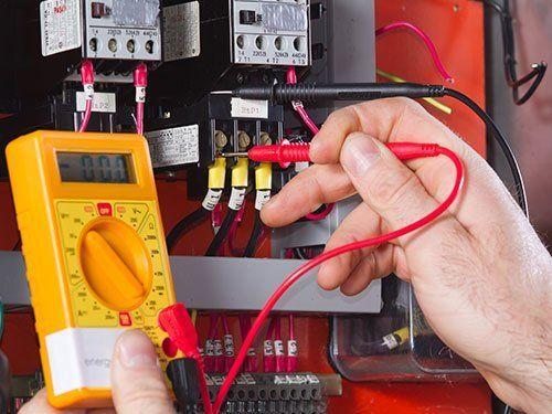 una mano che testa un quadro elettrico con un tester