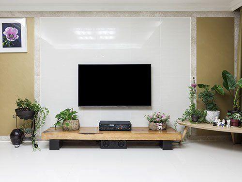 una tv a muro e  davanti un tavolino con degli oggetti