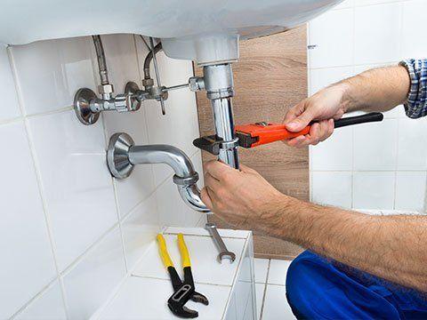 mani di un operaio che stringe un tubo di un lavandino