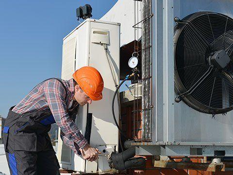 un tecnico che sistema un motore di un condotto di ventilazione