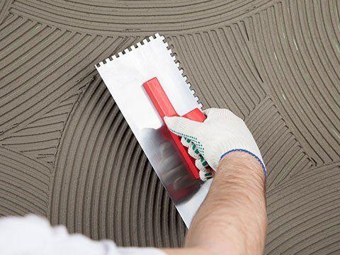 una mano con una spatola durante una decorazione su del cemento fresco