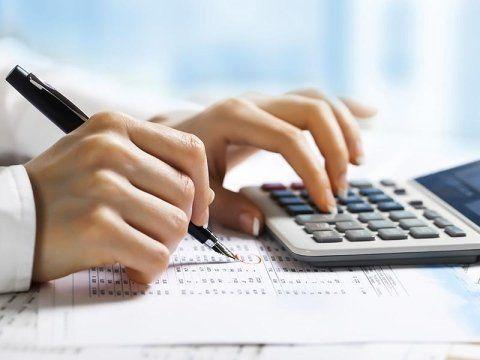 una mano con una penna e un'altra che usa una calcolatrice