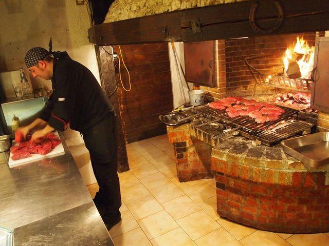 Chef prepara la carne vicino al focolare