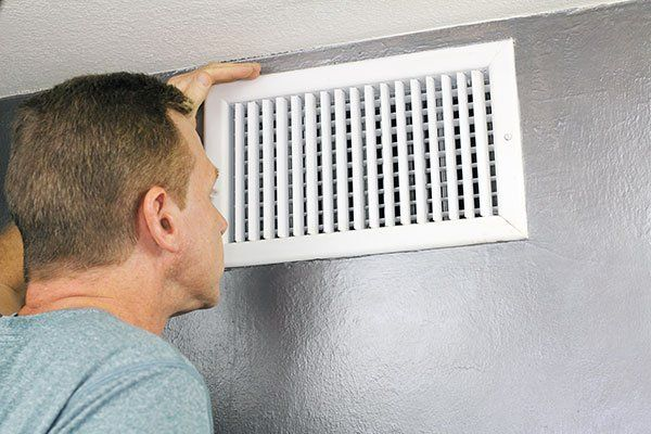 Man examining an outflow air vent