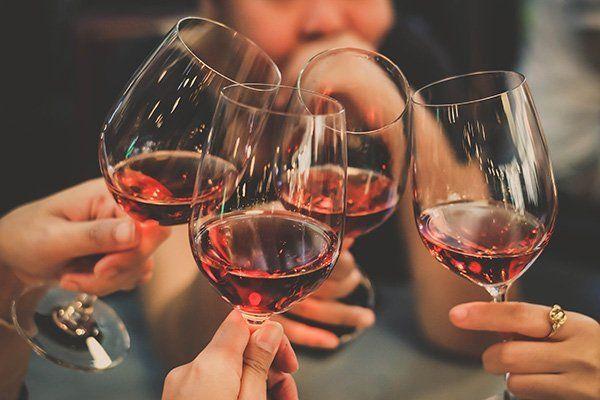 brindisi con 4 bicchieri di vino rosso